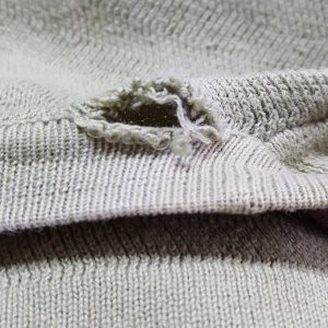 Hole in the neck seam of a jumper needs a repair and rescue service
